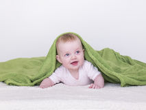 Baby girls with blanket green. Baby girl playing on the bed with a blanket over his head Stock Images