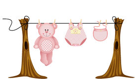 Baby girls clothing with teddy bear on clothesline Royalty Free Stock Image
