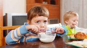 Baby girls eating dairy breakfast Stock Photo