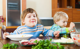 Baby girls eating food from plates Royalty Free Stock Image