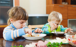 Baby girls eating at wooden table Stock Photos