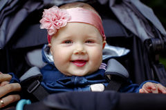 Baby girls smiling face, close-up outdoor. Baby sitting in a baby carriage, holding my mother's finger, a bandage on his head with a pink flower. Baby smiling Stock Photography