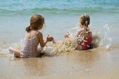 Baby girls swimming near beach. Stock Photo