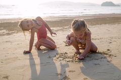 Baby girls swimming near beach. Royalty Free Stock Images