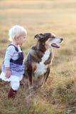 Baby Girls Talking to German Shepherd Dog Outside at Sunset Royalty Free Stock Photos