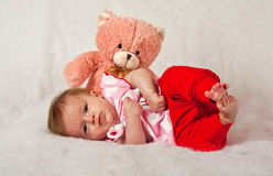 Baby girly lying in front of a pink teddie Royalty Free Stock Photography