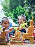 Baby give water to Buddha Stock Photo