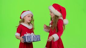 Baby gives a New Year gift to her friend. Green screen. Slow motion. Baby in a red suit gives a New Year`s gift a surprise to her friend. Green screen. Slow stock footage