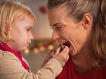 Baby giving mother bite of chocolate santa. In kitchen stock images