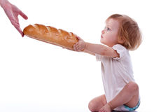 Baby giving out a loaf of bread Royalty Free Stock Photo