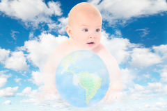 Baby with glass globe on clouds in sky Royalty Free Stock Images