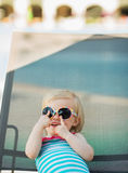 Baby in glasses laying on sun bed Stock Images
