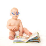 Baby in glasses reading book and learning. Isolated on white background Royalty Free Stock Photo