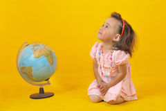Baby and globe. On the yellow background Royalty Free Stock Image