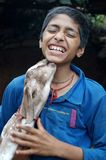 Baby Goat kissing a boy. A baby goat is kissing and playing with a boy in rural village of Nepal stock photo
