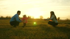 Baby goes on lawn from dad to mom. child takes first steps in park. mom and dad play with kid on the grass at sunset. Baby goes on lawn from dad to mom. child stock images