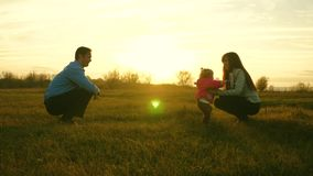 Baby goes on lawn from dad to mom. child takes first steps in park. mom and dad play with kid on the grass at sunset. Baby goes on lawn from dad to mom. child royalty free stock photos