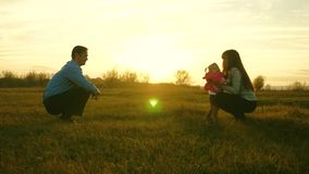 Baby goes on lawn from dad to mom. child takes first steps in park. mom and dad play with kid on the grass at sunset. Baby goes on lawn from dad to mom. child royalty free stock photo