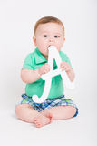 Baby Going to Chew Letter A. 8 month year old baby sits on a white background holding a white letter A about to place in his mouth. dressed in a cute green polo Royalty Free Stock Photos