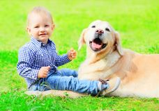 Baby and Golden Retriever dog is sitting together on the grass. On a summer stock photo