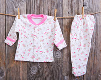 Baby goods hanging on the clothesline. Baby blouse and pants sliders on the clothespin on the rope. On a wooden background Royalty Free Stock Photos