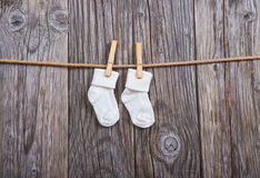 Baby goods hanging on the clothesline. Baby white socks on a clothespin. On a wooden background Royalty Free Stock Images
