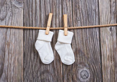 Baby goods hanging on the clothesline. Baby white socks on a clothespin. On a wooden background Stock Image