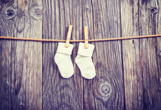 Baby goods hanging on the clothesline. Baby white socks on a clothespin. On a wooden background Royalty Free Stock Photos