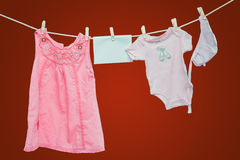 Baby goods hanging on the clothesline. On red background Stock Photo
