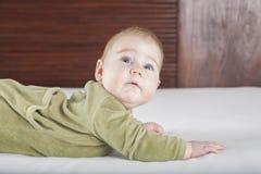 Baby grünes onesie, das überrascht schaut Stockfotografie