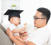 Baby with graduation cap holding certificate. Asian family lifestyle at home. Baby with graduation cap holding certificate. Child and father early education Stock Photos