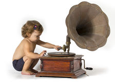 Baby and Gramophone. Baby girl sits and plays with an old gramophone Stock Photos