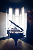 A Baby Grand Piano in a Bay Window Royalty Free Stock Photography