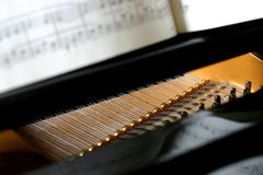 Baby grand piano detail. Detail of interior damper strings inside a black baby grand piano; focus on strings with sheet music and its reflections royalty free stock photography