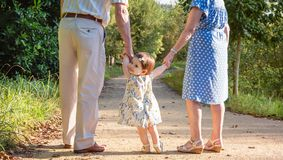 Baby granddaughter walking with her grandparents outdoors stock images