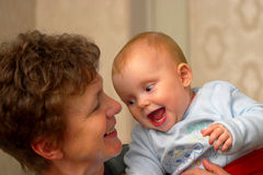Baby with grandma. Baby and grandma smiling and laughing to each other Royalty Free Stock Photography