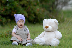 Baby on the grass. With a bear toy stock images