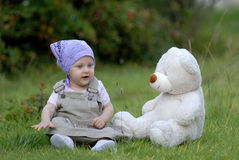 Baby on the grass. With a bear toy Royalty Free Stock Photos