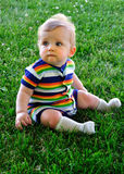 Baby on Grass. Adorable infant sits on a field of green grass Stock Image