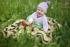 Baby on the grass, in the jumper and booties Stock Photography