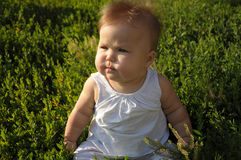Baby on the grass, wind blowing Royalty Free Stock Image