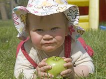 Baby with green apple. Baby with sun hat and a green apple in the meadow Stock Image