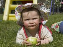 Baby with green apple. Baby with sun hat and a green apple in the meadow Royalty Free Stock Photos