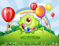 A baby green monster at the hilltop with a rainbow Stock Photography