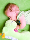 Baby with green toy. Baby girl lying on a green blanket playing with her soft toy giraffe Stock Photo