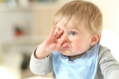 Baby grimacing with a hand on the face Royalty Free Stock Photo