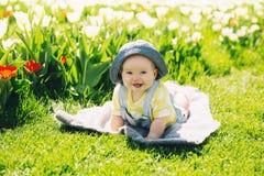 Baby in groen gras van tulpengebied bij de lente stock fotografie
