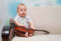 Baby with guitar sit on couch Royalty Free Stock Image