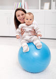 Baby gymnastic and fun. With mother and large ball Royalty Free Stock Photos