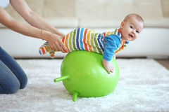 Baby gymnastic. Baby playing with gymnastic ball with mother at home Royalty Free Stock Images